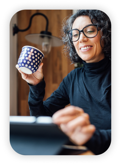 Lady using tablet and sipping coffee