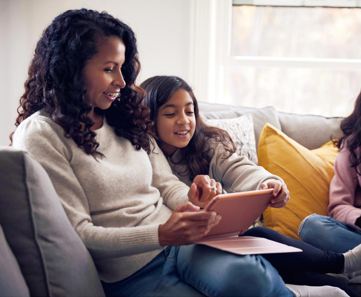 mother-and-daughter-cuddling-on-couch-with-device-v2